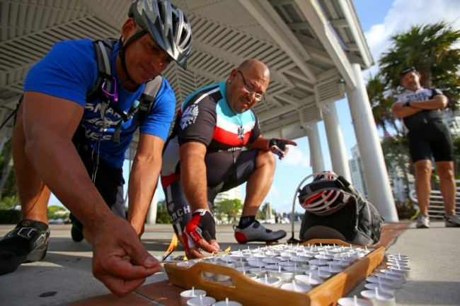 fl-clo-ride-of-silenceHenry Castelo (left) and Ted Rivera light candles at Esplanade Park in Fort Lauderdale during the Ride of Silence on May 21, 2014. The ceremony is a part of an annual event where cyclists take to the roads in a silent procession to